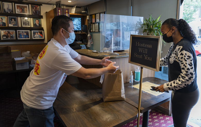 Benny Yun, owner of Yang Chow restaurant, left, delivers a take-out order in Los Angeles, Thursday, Dec. 17, 2020. Bigotry toward Asian Americans and Asian food has spread steadily alongside the coronavirus in the United States. Yun said even though his businesses have survived the pandemic, they get prank calls almost daily asking if they have dog or cat on the menu or impersonating a thick Asian accent. (AP Photo/Damian Dovarganes)