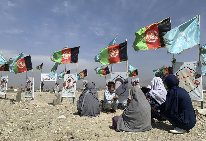 FILE – In this Sept 14, 2020 file photo, families and friends of students who were killed in local conflicts gather at the graves of their relatives, adorned with their pictures, on the outskirts of Kabul, Afghanistan. The Watson Institute of International and Public Affairs, a research center at Brown University, said in its report on Tuesday, Dec. 8, 2020 that there has been a dramatic increase in airstrikes conducted by Afghan government forces from July to September this year, attacks that have led to a sharp rise in civilian casualties. (AP Photo/Rahmat Gul, File)