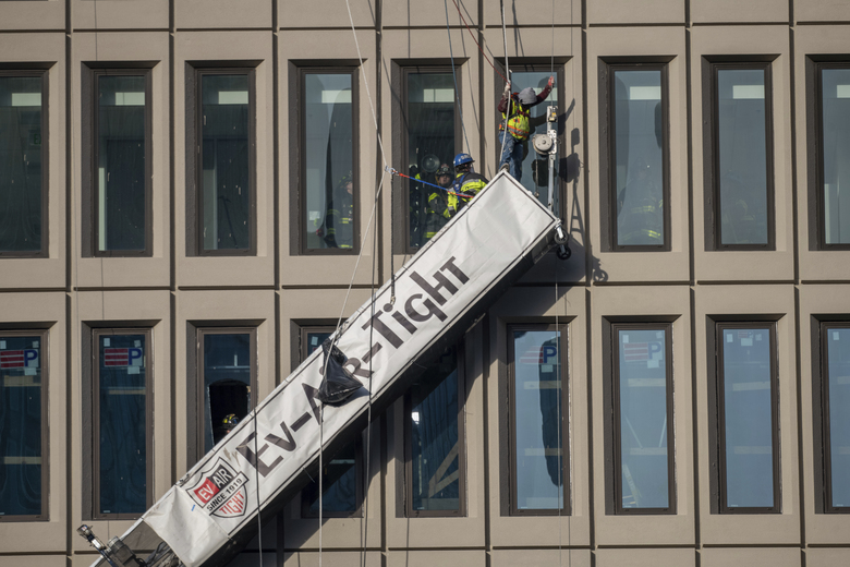 A worker stands on the end of a dangling scaffold as he waits to be rescued following an explosion at Baltimore Gas and Electric's offices, Wednesday, Dec. 23, 2020.  Twenty-one of the victims were brought to area hospitals following the explosion with a partial roof collapse. The city's fire department tweeted that at least nine of the victims were in critical condition, while another was in serious condition. (Jerry Jackson/The Baltimore Sun via AP)