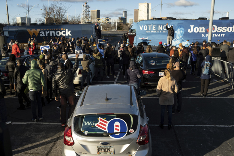 Democratic Georgia Senate challengers Rev. Raphael Warnock and Jon Ossoff hold a rally in Atlanta on the first day of early voting for the senate runoff Monday, Dec. 14, 2020. (AP Photo/Ben Gray)