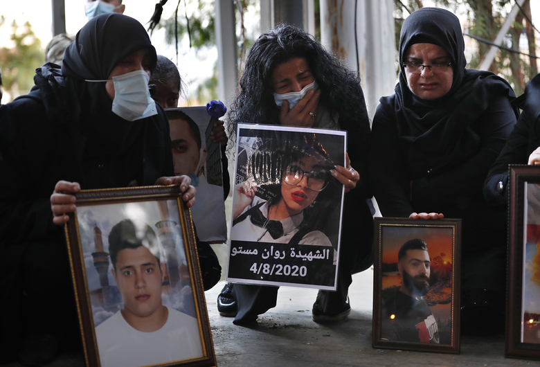 Relatives of victims of the Aug. 4 Beirut port explosion hold portraits of their loved one who killed during the explosion, during a vigil at the seaport main entrance, as they marking four months since the blast that killed more than 200 people and injured thousands, in Beirut, Lebanon Friday, Dec. 4, 2020. An investigation has yet to provide answers or hold any senior official responsible and the victims are demanding answers and justice for their loved ones. (AP Photo/Hussein Malla)