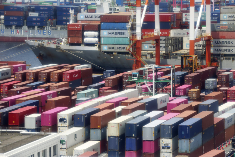 FILE – In this June 17, 2020, file photo, containers are piled up at a port in Yokohama, south of Tokyo. A quarterly survey by the Bank of Japan shows business sentiment has improved sharply with expectations that the economy is recovering from a year-long recession.(AP Photo/Koji Sasahara, File)