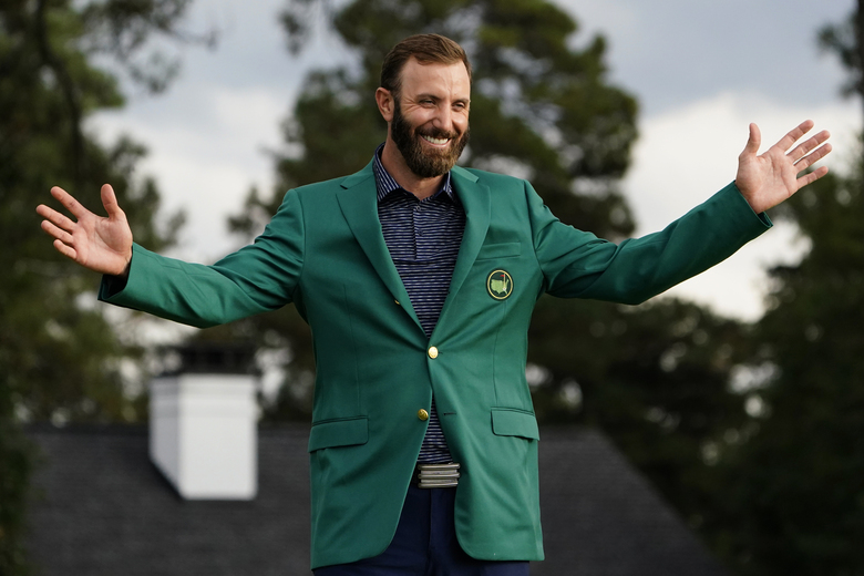 FILE – Masters golf champion Dustin Johnson shows off his green jacket after his victory in Augusta, Ga., in this Sunday, Nov. 15, 2020, file photo. Johnson was sure to send Phil Mickelson a text about his whereabouts next year the night of the champions dinner. (AP Photo/Matt Slocum, File)