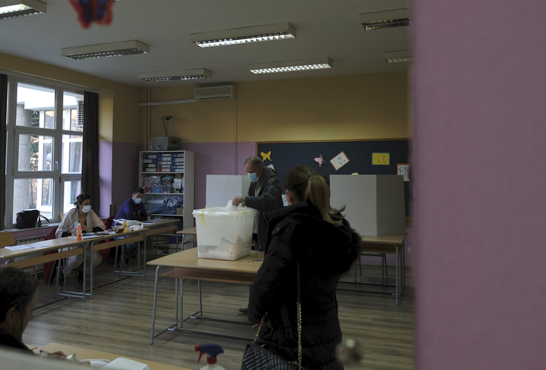 A man reflected in a mirror casts his ballot for the local elections at a polling station in Mostar, Bosnia, Sunday, Dec. 20, 2020. Divided between Muslim Bosniaks and Catholic Croats, who fought fiercely for control over the city during the 1990s conflict, Mostar has not held a local poll since 2008, when Bosnia's constitutional court declared its election rules to be discriminatory and ordered that they be changed. (AP Photo/Kemal Softic)