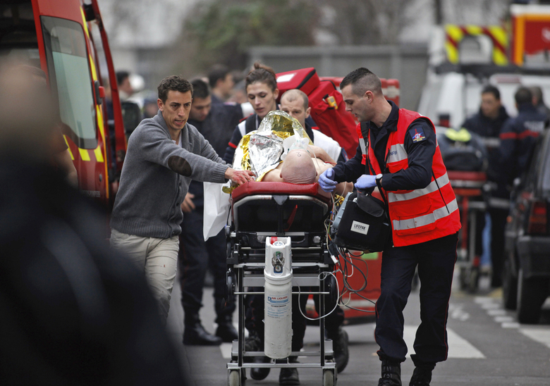 FILE – In this Jan. 7, 2015, file photo, an injured person is transported to an ambulance after a shooting at the French satirical newspaper Charlie Hebdo's office in Paris, France. The terrorism trial of 14 people linked to the January 2015 Paris attacks on the satirical weekly Charlie Hebdo and a kosher supermarket ends Wednesday after three months punctuated by new attacks, a wave of coronavirus infections among the defendants, and devastating testimony bearing witness to three days of bloodshed that shook France.(AP Photo/Thibault Camus, File)