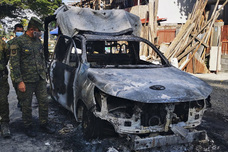 Police wearing to prevent the spread of the coronavirus check a burned patrol car in Datu Piang, Maguindanao province, southern Philippines on Friday Dec. 4, 2020. Dozens of Muslim militants aligned with the Islamic State group opened fire on a Philippine army detachment and burned a police patrol car in a southern town but withdrew after troops returned fire, officials said Friday. (AP Photo/Ferdinandh Cabrera)