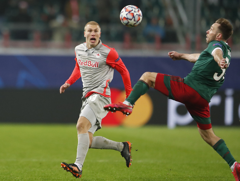 Salzburg's Rasmus Kristensen, left, and Lokomotiv's Maciej Rybus challenge for the ball during the Champions League, group A, soccer match between Lokomotiv Moscow and RB Salzburg at the Lokomotiv stadium in Moscow, Russia, Tuesday, Dec. 1, 2020. (Maxim Shemetov/Pool via AP)