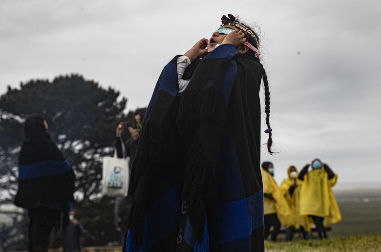 Magdalena Nahuelpan, a Mapuche Indigenous girl, looks at a total solar eclipse through an overcast sky using special paper and plastic glasses in Carahue, La Araucania, Chile, Monday, Dec. 14, 2020. The total eclipse was visible from Chile and the northern Patagonia region of Argentina, and as a partial solar eclipse in Bolivia, Brazil, Ecuador, Paraguay, Peru and Uruguay. (AP Photo/Esteban Felix)