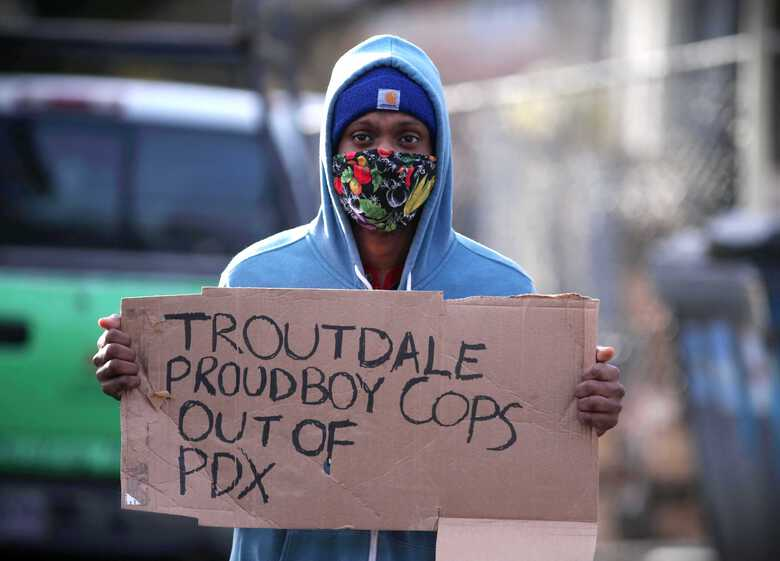 A protester holds up a sign during a demonstration Tuesday  to express outrage against gentrification and the eviction of the Black and Indigenous family in September in Portland, Oregon. (Beth Nakamura/The Oregonian)