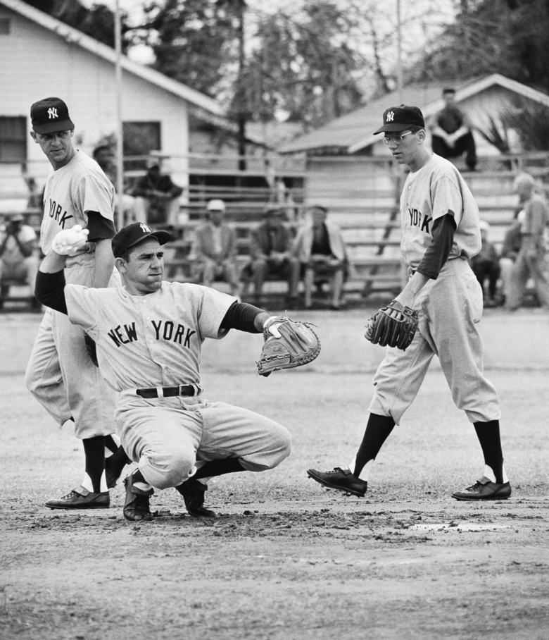 FILE – In this February 1958 file photo, New York Yankee catcher Yogi Berra, troubled with a skin infection, wears white gloves to protect his hands as he warms up a pitcher during baseball spring training in St. Petersburg, Fla. Walking behind Yogi are outfielder John Reed and infielder Phil Linz, right. Linz, who knocked a Game 7 home run off Bob Gibson in the 1964 World Series but made even more noise by hitting a few sour notes on his harmonica, has died. He was 81. Former teammates said Linz's family told them he died Wednesday night, Dec. 9, in Leesburg, Va. Linz had been in poor health since a stroke five years ago. (AP Photo/Harry Harris, File)