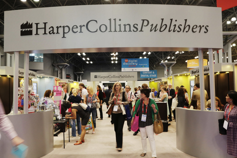 FILE – In this May 28, 2015 file photo, attendees at BookExpo America visit the HarperCollins Publishers booth in New York. The annual publishing convention and trade show, a decades-old tradition, may be coming to an end. ReedPop, which has managed BookExpo for a quarter century, announced Tuesday that it was dropping the event, along with the fan-based BookCon. (AP Photo/Mark Lennihan, File)