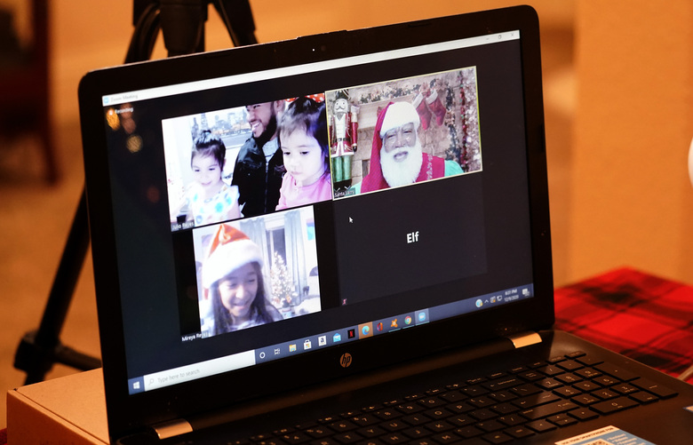 Larry Jefferson, right, portrays Santa Claus and conducts a visit via a computer screen with Raquel Anaya, bottom left, and her cousins Lexi Reyes, top left, and Luna Reyes from his home in Duncanville, Texas, on Dec. 9, 2020. The children lost a grandmother to COVID-19 recently. In this socially distant holiday season, Santa Claus is still coming to towns (and shopping malls) across America but with a few 2020 rules in effect. (AP Photo/LM Otero)