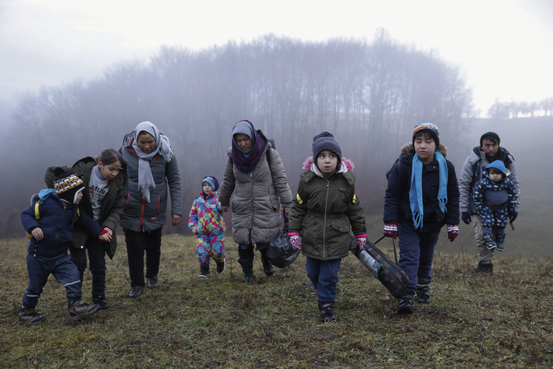 FILE – In this Thursday Dec. 10, 2020 file photo, two Afghan families walk in a clearing after leaving a Croatian forest near the Bosnian town of Velika Kladusa. The European Union on Monday Dec. 21, 2020, warned Bosnia that thousands of migrants face a winter without shelter, and it urged the country's bickering political authorities to set aside their differences and take action. (AP Photo/Marc Sanye, File)