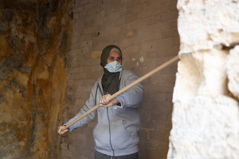A female artist volunteer renovates a room of the long-abandoned 200-year-old al-Kamalaia school, in the old quarter of Gaza City, Sunday, Dec. 20, 2020. Less than 200 of these old houses are still partly or entirely standing, according to officials and they are threatened by neglect, decaying and urban sprawl. (AP Photo/Adel Hana)
