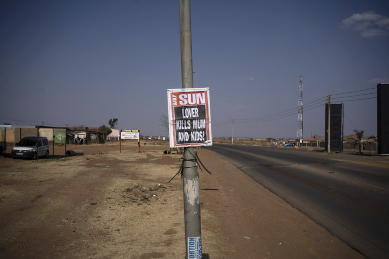 """A poster with a local newspaper headline, """"Lover Kills Mum and Kids!"""" is affixed to a pole on the side of a road in Johannesburg, South Africa, on Aug. 26, 2020. According to official figures, around 1,000 kids are murdered every year in South Africa, nearly three a day. But that statistic, horrific as it is, may be an undercount. (AP Photo/Bram Janssen)"""