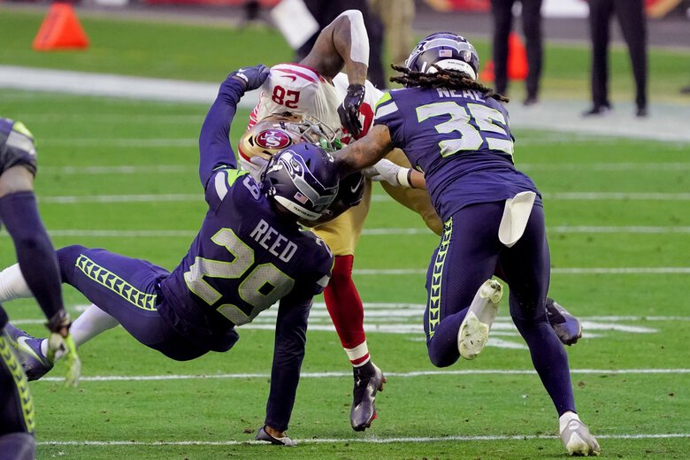 San Francisco 49ers running back Jerick McKinnon (28) is hit by Seattle Seahawks free safety D.J. Reed (29) and Seattle Seahawks strong safety Ryan Neal (35) during the second half of an NFL football game, Sunday, Jan. 3, 2021, in Glendale, Ariz. (Rick Scuteri / The Associated Press)