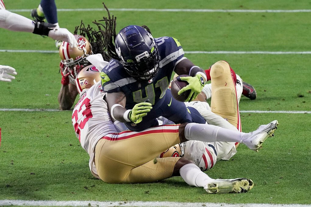 Seattle Seahawks running back Alex Collins scores a touchdown as San Francisco 49ers defensive back Tarvarius Moore (33) defends during the second half of an NFL football game, Sunday, Jan. 3, 2021, in Glendale, Ariz.  (Ross D. Franklin / The Associated Press)