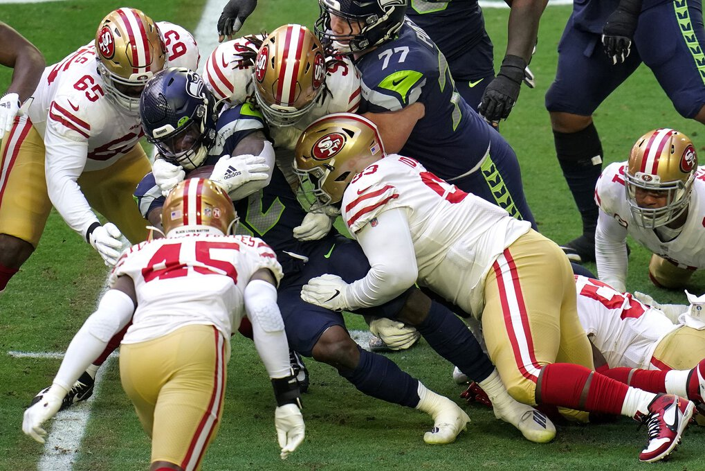 Seattle Seahawks running back Chris Carson (32) is stopepd by San Francisco 49ers defensive tackle D.J. Jones (93), middle linebacker Fred Warner (54) and defensive tackle Darrion Daniels (65) during the first half of an NFL football game, Sunday, Jan. 3, 2021, in Glendale, Ariz.  (Ross D. Franklin / The Associated Press)