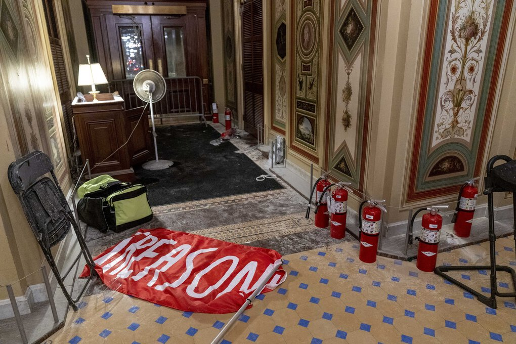 """A flag that reads """"Treason"""" lies on the floor in the Capitol on Jan. 7, 2021. (Andrew Harnik / The Associated Press)"""