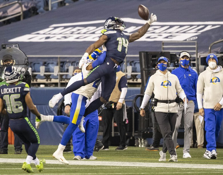 DK Metcalf has to go high for the pass that's just out of his reach in the 4th. (Dean Rutz / The Seattle Times)