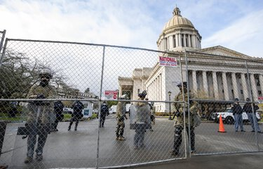 The Washington National Guard and the Washington State Patrol stand guard at the perimeter fence erected around  the State Capitol in Olympia Sunday January 10, 2021, the day before the start of the legislative session. 216086