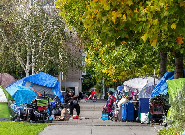 Tents from a homeless encampment are seen lining the sidewalks at Ballard Commons Park in Seattle on October 26, 2020. (Mike Siegel / The Seattle Times)