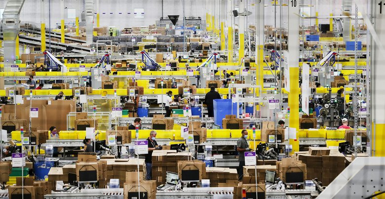 Amazon has long opposed the unionization of its U.S. workforce. Above, employees at packing stations at Amazon's Kent fulfillment center in June. (Ken Lambert / The Seattle Times)