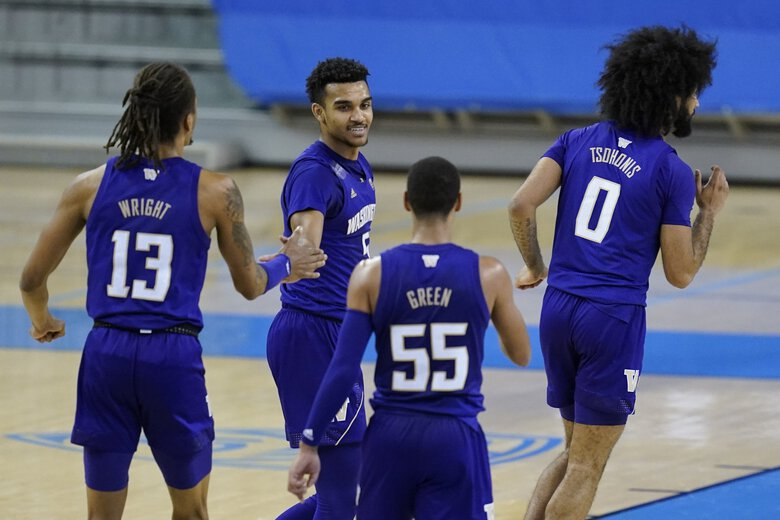 Washington forward Hameir Wright (13), guard Jamal Bey (5), guard Quade Green (55), and guard Marcus Tsohonis (0) celebrate being 10 points ahead of UCLA at halftime of an NCAA college basketball game Saturday, Jan. 16, 2021, in Los Angeles.(Ashley Landis / The Associated Press)