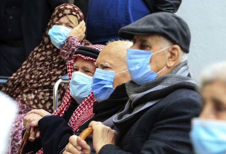 People wait to receive a Pfizer vaccine at a vaccination center, in Amman, Jordan, Wednesday, Jan. 13, 2021. Jordan has begun administering coronavirus vaccines with the goal of inoculating 10,000 people in the first two days. (Raad Adayleh / The Associated Press)