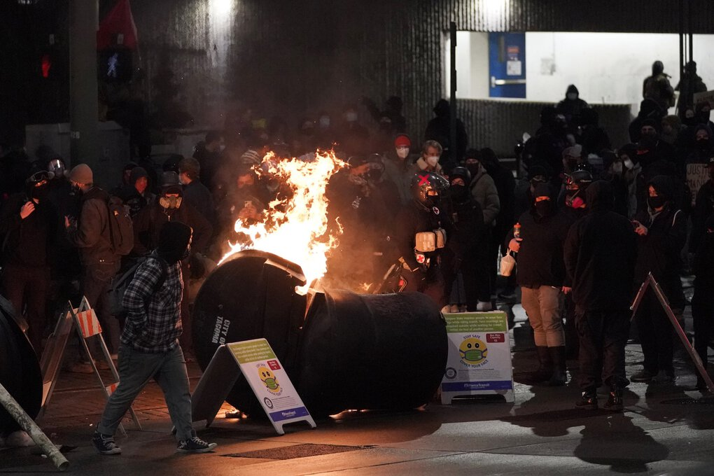 A trash can burns as people take part in a protest against police brutality, late Sunday, Jan. 24, 2021, in downtown Tacoma. The protest came a day after at least two people were injured when a Tacoma Police officer responding to a report of a street race drove his car through a crowd of pedestrians that had gathered around him. Several people were knocked to the ground and at least one person was run over. (Ted S. Warren / The Associated Press)