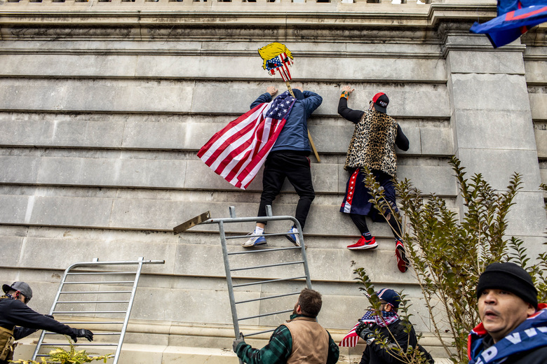 Members of a pro-Trumb mob climb the Capitol in Washington on Wednesday, Jan. 6, 2021. As star-spangled superheroes and militiamen, the rioters of D.C. dressed with a license for mayhem. (Jason Andrew/The New York Times)
