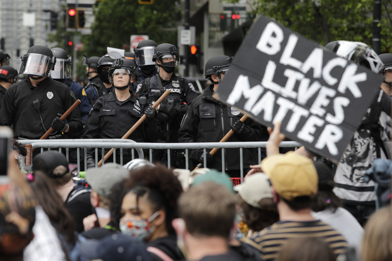 Police officers behind a barricade look on as protesters fill the street in front of Seattle City Hall in June 2020, following the death of George Floyd. (AP Photo / Elaine Thompson, File)