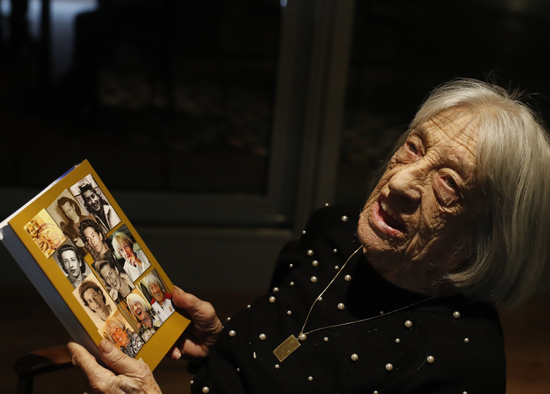 Agnes Keleti, former Olympic gold medal winning gymnast, holds a book with portraits of her on the back cover in Budapest, Hungary Monday Jan. 4, 2021. The oldest living Olympic champion turns 100 and says the fondest memory of her remarkable life is simply that she has lived through it all. Keleti had her illustrious career interrupted by World War II and the subsequent cancellation of the 1940 and 1944 Olympics. (AP Photo/Laszlo Balogh)