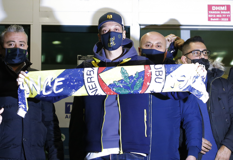 Mesut Ozil, former Germany midfielder poses for the photographers with a Fenerbahce scarf after arriving at the Ataturk Airport in Istanbul, early Monday, Jan. 18, 2021. Ozil, who is of Turkish descent, will look to reignite his career in Turkey after he left Arsenal to join Fenerbahce. (AP Photo)
