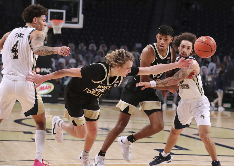 Wake Forest guard Carter Whitt loses control of the ball on a drive against Georgia Tech guards Jordan Usher, left, and Jose Alvarado, right, during an NCAA college basketball game on Sunday, Jan. 3, 2021, in Atlanta.  (Curtis Compton/Atlanta Journal-Constitution via AP)