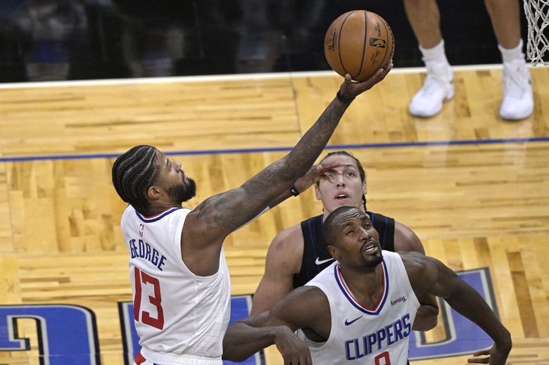 Los Angeles Clippers guard Paul George (13) shoots in front of center Serge Ibaka (9) and Orlando Magic forward Aaron Gordon, rear, during the first half of an NBA basketball game, Friday, Jan. 29, 2021, in Orlando, Fla. (AP Photo/Phelan M. Ebenhack)