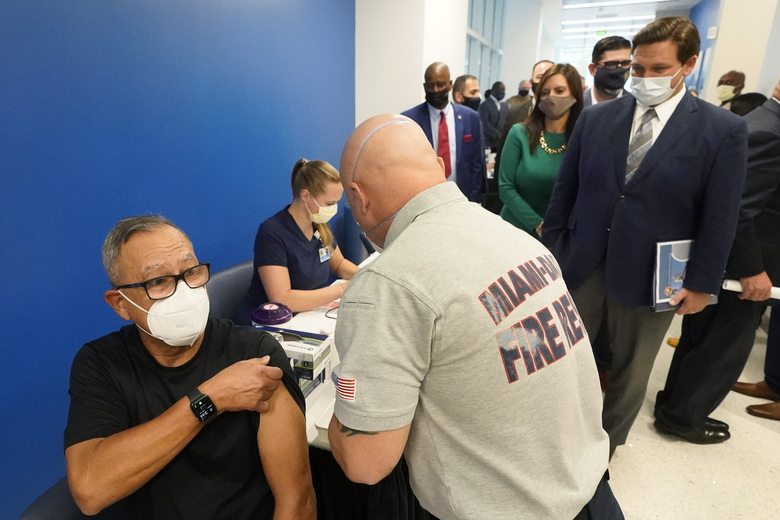 FILE – In this Jan. 4, 2021, file photo, Florida Gov. Ron DeSantis, right rear, watches as Carlos Dennis, left, 65, rolls up his sleeve so that Miami-Dade County Fire Rescue paramedic, Capt. Javier Crespo, can administer a COVID-19 vaccine shot at Jackson Memorial Hospital in Miami. With frustration rising over the slow rollout of the vaccine, state leaders and other politicians are turning up the pressure, improvising and seeking to bend the rules to get shots in arms more quickly. (AP Photo/Wilfredo Lee, File)