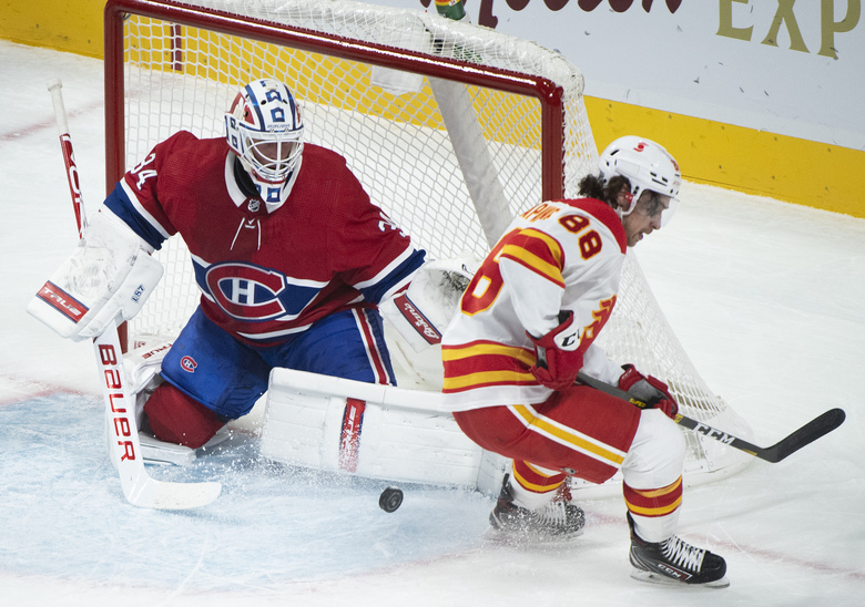 Calgary Flames' Andrew Mangiapane (88) moves in on Montreal Canadiens goaltender Jake Allen during first-period NHL hockey game action in Montreal, Saturday, Jan. 30, 2021. (Graham Hughes/The Canadian Press via AP)