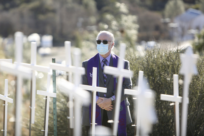 Senior Minister Rev. Rafe Ellis, of Sierra Center for Spiritual Living, gets a close look at the COVID Memorial placed on the Old Barn Self Storage property adjacent to the Golden Center Freeway Tuesday, Jan. 19, 2021 in Grass Valley, Calif. Ellis was one of three local ministers to speak during a commemoration of the memorial in which family of the deceased attended. (Elias Funez/The Union via AP)