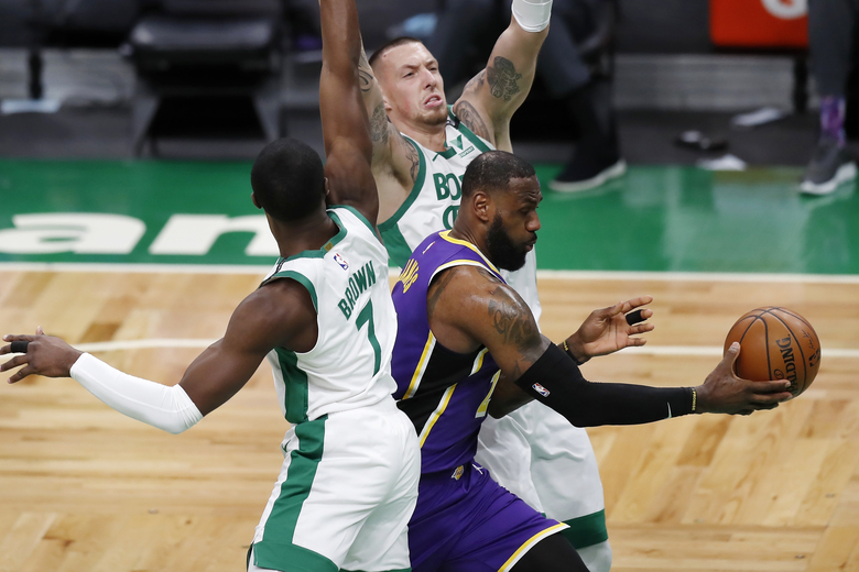 Boston Celtics' Daniel Theis, behind, and Jaylen Brown (7) defend against Los Angeles Lakers' LeBron James during the first half of an NBA basketball game Saturday, Jan. 30, 2021, in Boston. (AP Photo/Michael Dwyer)