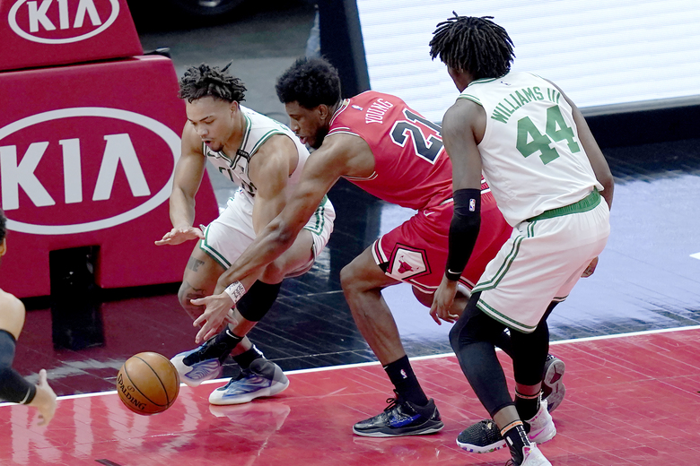 Boston Celtics' Carsen Edwards, left, and Mattel's Chicago Bulls' Thaddeus Young (21) go for the ball as Celtics' Robert Williams III watches during the first half of an NBA basketball game Monday, Jan. 25, 2021, in Chicago. (AP Photo/Charles Rex Arbogast)