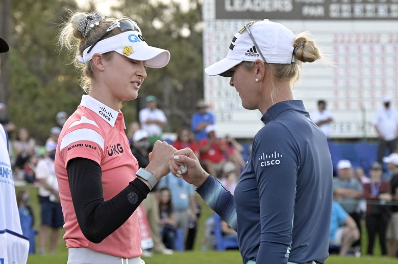 Jessica Korda, right, gets a fist-bump from her sister Nelly Korda on the 18th green after forcing a playoff against Danielle Kang during the final round of the Tournament of Champions LPGA golf tournament, Sunday, Jan. 24, 2021, in Lake Buena Vista, Fla. (AP Photo/Phelan M. Ebenhack)