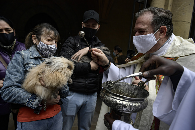 Manoli, left, wearing a face mask to prevent the spread of the coronavirus, holds her rabbit while Priest Cesar Magana blesses her pet during the feast of St. Anthony, Spain's patron saint of animals, in Pamplona, northern Spain, Sunday, Jan. 17, 2021. The feast is celebrated each year in many parts of Spain and people bring their pets to churches to be blessed. (AP Photo/Alvaro Barrientos)