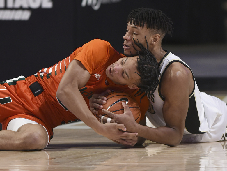 CORRECTS ID TO MIAMI'S ISAIAH WONG, NOT MIAMI'S DONALD CHANEY JR.  – Miami's Isaiah Wong, left, and Wake Forest's Ody Oguama battle for a loose ball in an NCAA college basketball game, Saturday, Jan. 30, 2021, at Joel Coliseum in Winston-Salem, N.C. (Walt Unks/The Winston-Salem Journal via AP)