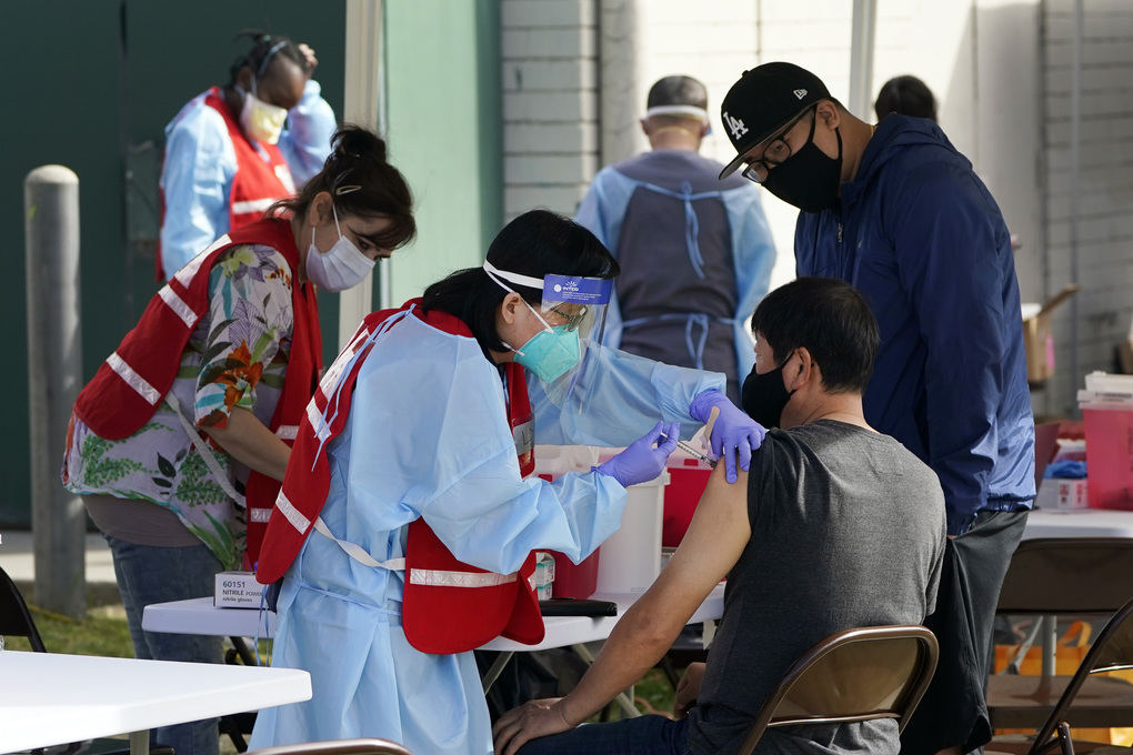 FILE – In this Jan. 13, 2021, file photo, health care workers receive a COVID-19 vaccination at Ritchie Valens Recreation Center, Wednesday, Jan. 13, 2021, in Pacoima, Calif. The rapid expansion of vaccinations to senior citizens across the U.S. has led to bottlenecks, system crashes and hard feelings in many states because of overwhelming demand for the shots. (AP Photo/Marcio Jose Sanchez, File)