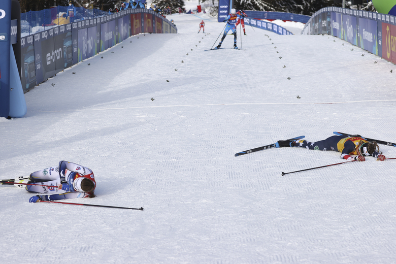 United States' Jessie Diggins, right, and Sweden's Ebba Andersson lie in the snow after completing a women's Tour de Ski, cross-country 10K mass start event, in Val di Fiemme, Italy, Sunday, Jan. 10, 2021. Diggins finished in second placed and clinched the Tour de Ski trophy. Andersson won the race as Diggins clinched the Tour de Ski trophy.(AP Photo/Alessandro Trovati)
