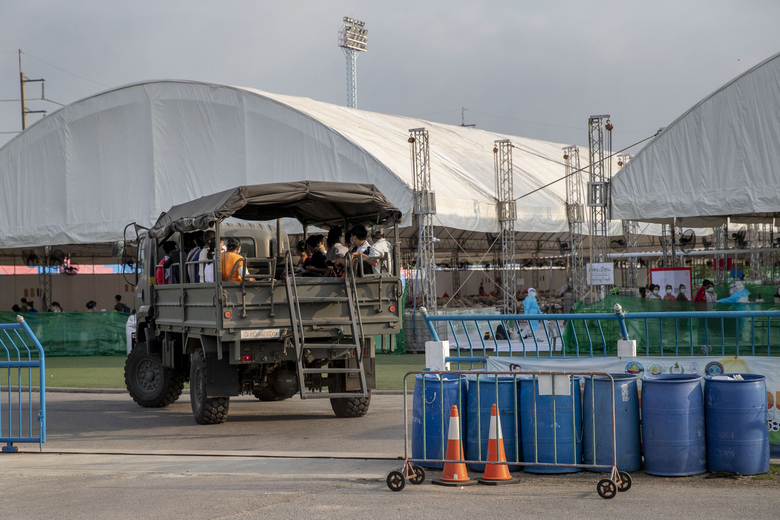 A truck carrying migrant workers and their families arrives at a field hospital for COVID-19 patents in Samut Sakhon, South of Bangkok, Thailand, Monday, Jan. 4, 2021. For much of 2020, Thailand had the coronavirus under control. After a strict nationwide lockdown in April and May, the number of new local infections dropped to zero, where they remained for the next six months. However, a new outbreak discovered in mid-December threatens to put Thailand back where it was in the toughest days of early 2020. (AP Photo/Gemunu Amarasinghe)