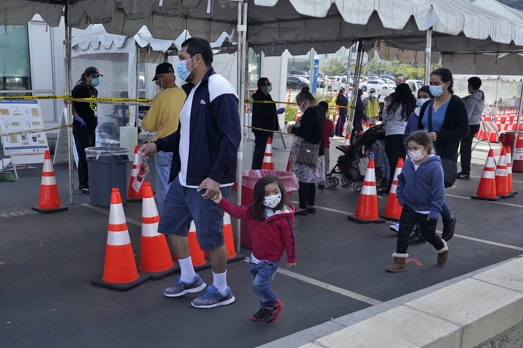 FILE – In this Jan. 7, 2021, file photo, people walk to a tent at a COVID-19 walk-up testing site on the Martin Luther King Jr. Medical Campus in Los Angeles, Jan. 7, 2021. Coronavirus deaths and cases per day in the U.S. dropped markedly over the past couple of weeks but are still running at alarmingly high levels, and the effort to snuff out COVID-19 is becoming an ever more urgent race between the vaccine and the mutating virus. (AP Photo/Marcio Jose Sanchez, File)