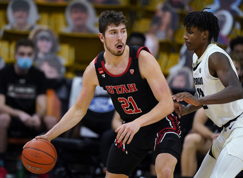 Utah forward Riley Battin, left, looks to pass the ball as Colorado forward Jabari Walker defends in the second half of an NCAA college basketball game Saturday, Jan. 30, 2021, in Boulder, Colo. (AP Photo/David Zalubowski)