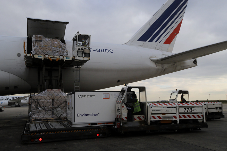 FILE – In this Wednesday, Nov. 25, 2020 file photo, Air France cargo workers load equipment and pharmaceutical containers onto a cargo plane at Roissy airport, outside Paris, as the company is preparing for the transport of COVID-19 vaccines. A last-minute trade deal with the United Kingdom coupled with the rollout of COVID-19 vaccines in the final days of the year produced a sense of success for the 27-nation bloc and brought glimmers of hope to the EU's 450 million residents. (AP Photo/Christophe Ena, File)